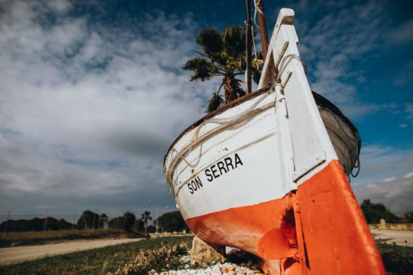 Old boat with the inscription Son Serra as entrance sign of the Mallorcan fishing village.