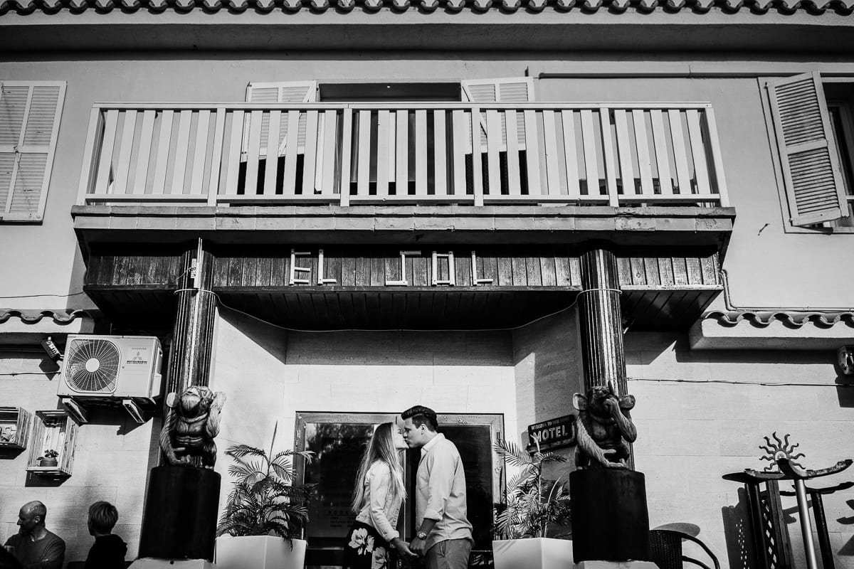 The bride and groom kissing in front of the entrance of the bar Sol in Son Serra.