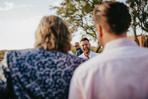A wedding guest laughs at the groom with all his heart.