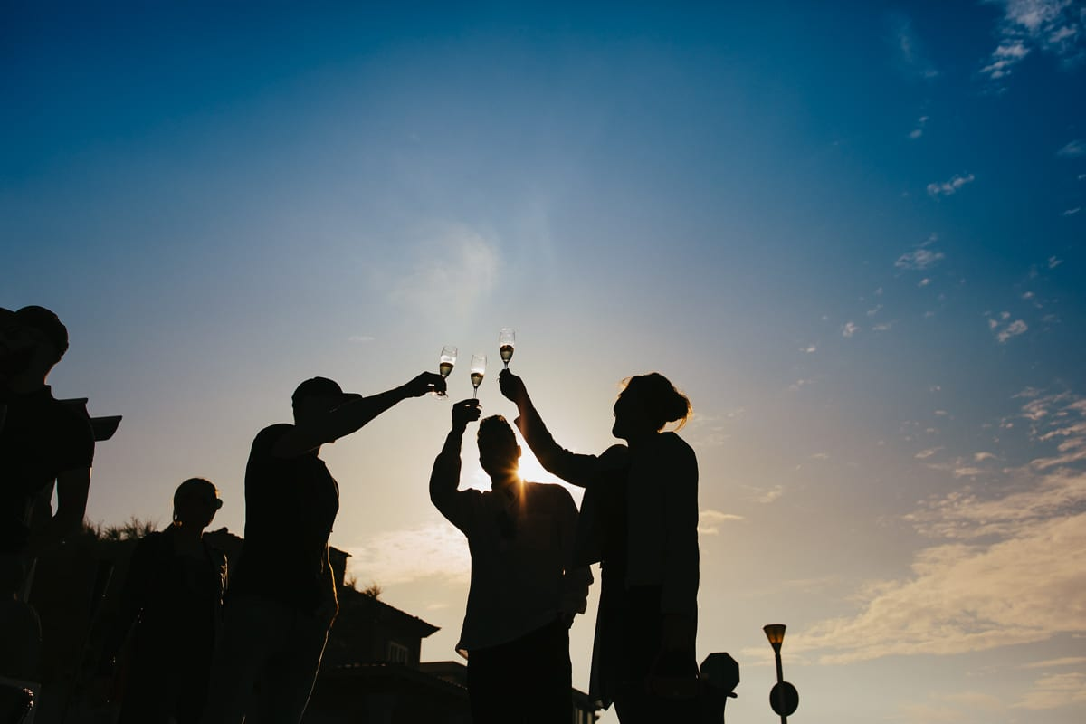 Silhouette picture of three guests toasting with a glass of sparkling wine.