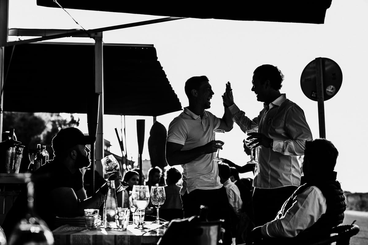 The brother of the groom and a guest give a hearty laugh high five.
