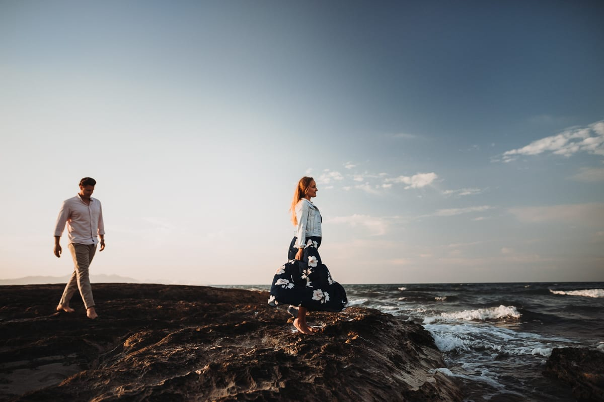 The bride is standing on brown rocks, looking out to sea and her groom is walking towards her.