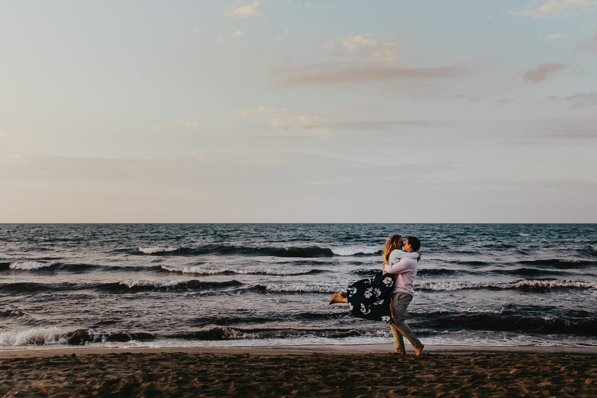 We see an overjoyed newlyweds in front of the sea. He lifts her up and turns.