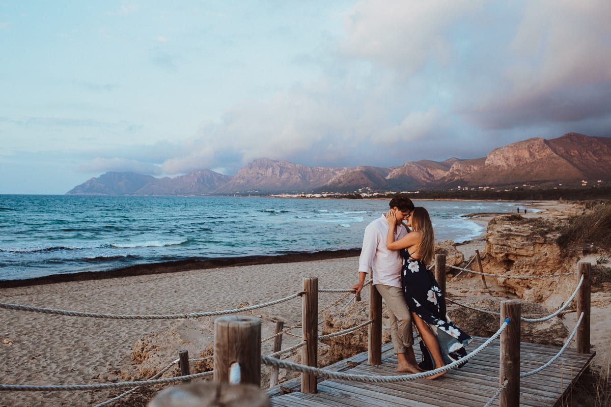 The bride and groom cuddle on the wooden walkway leading from the beach to the dunes. We see Majorca's wonderful blue sea and the mountains in the evening light in the background.