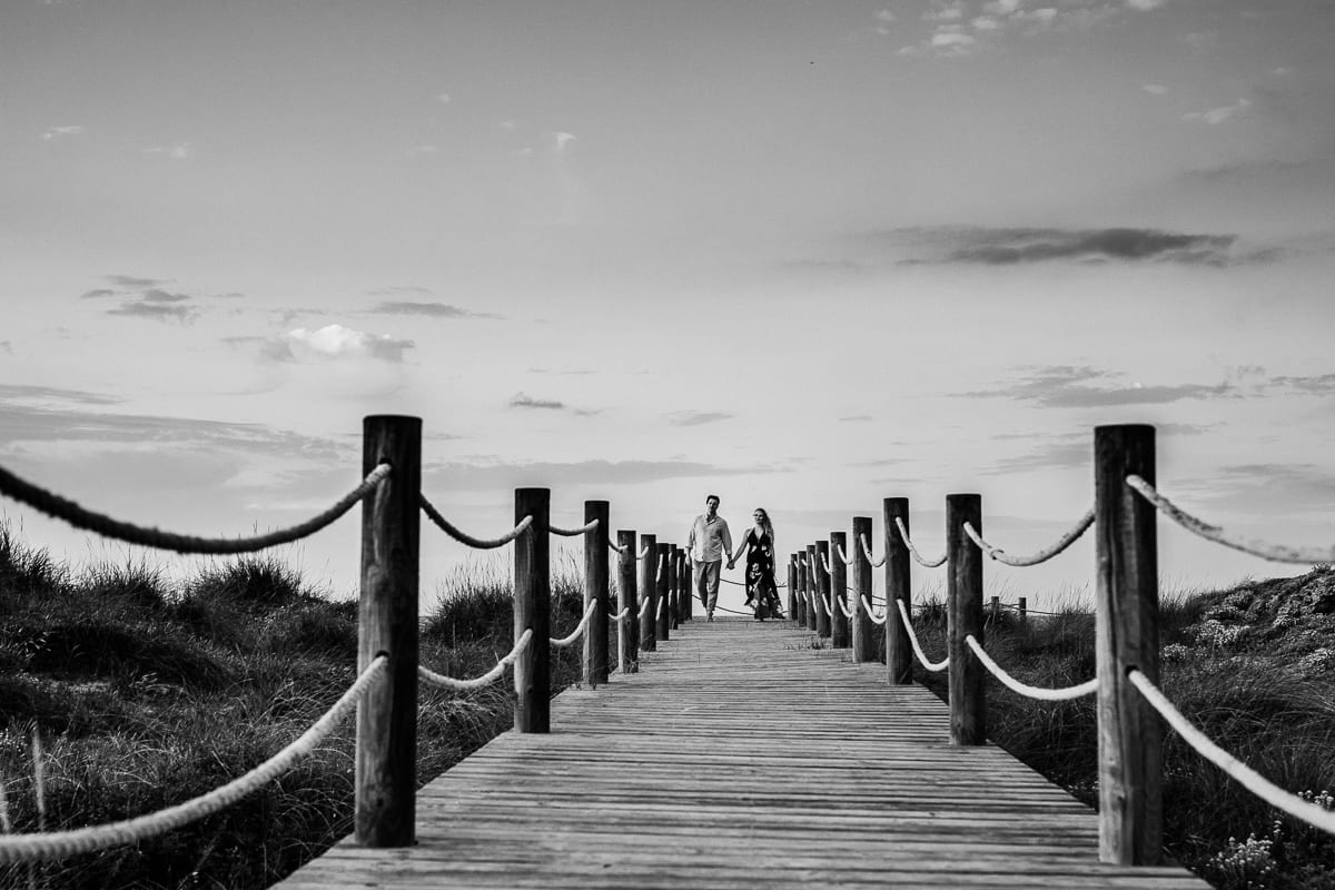 Black and white picture of the newlyweds on the wooden walkway.