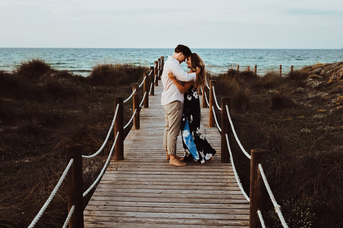 Both stopping in the middle of the boardwalk and look each other with love. We see the sea in the background.