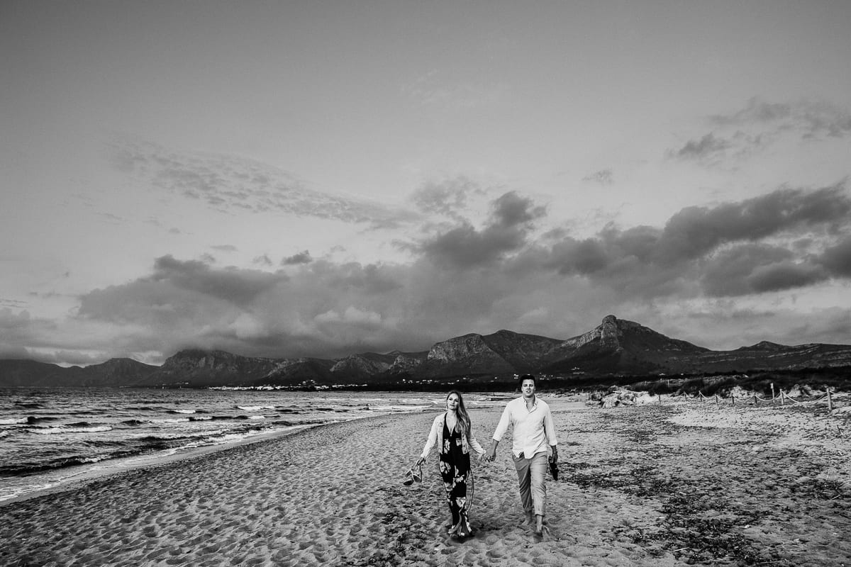 Black and white photo of bridal couple coming back from their beach walk.