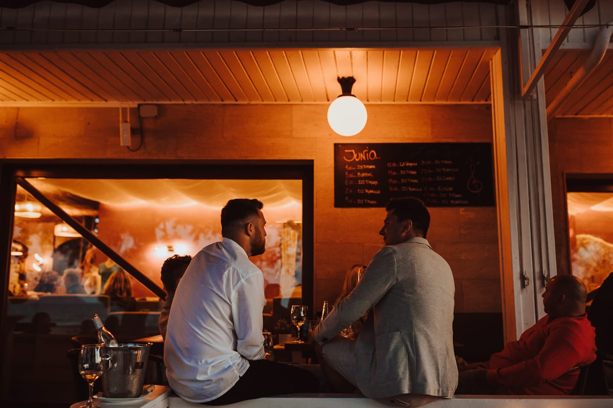 Two guests sitting on the parapet of the veranda of the bar and talk by warm lantern light.