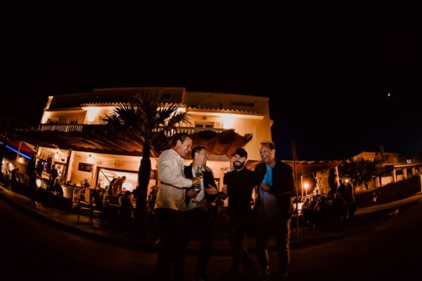 The brother of the groom and three friends laugh heartily in front of the illuminated Bar Sol in the fishing village of Son Serra de Marina in Majorca.