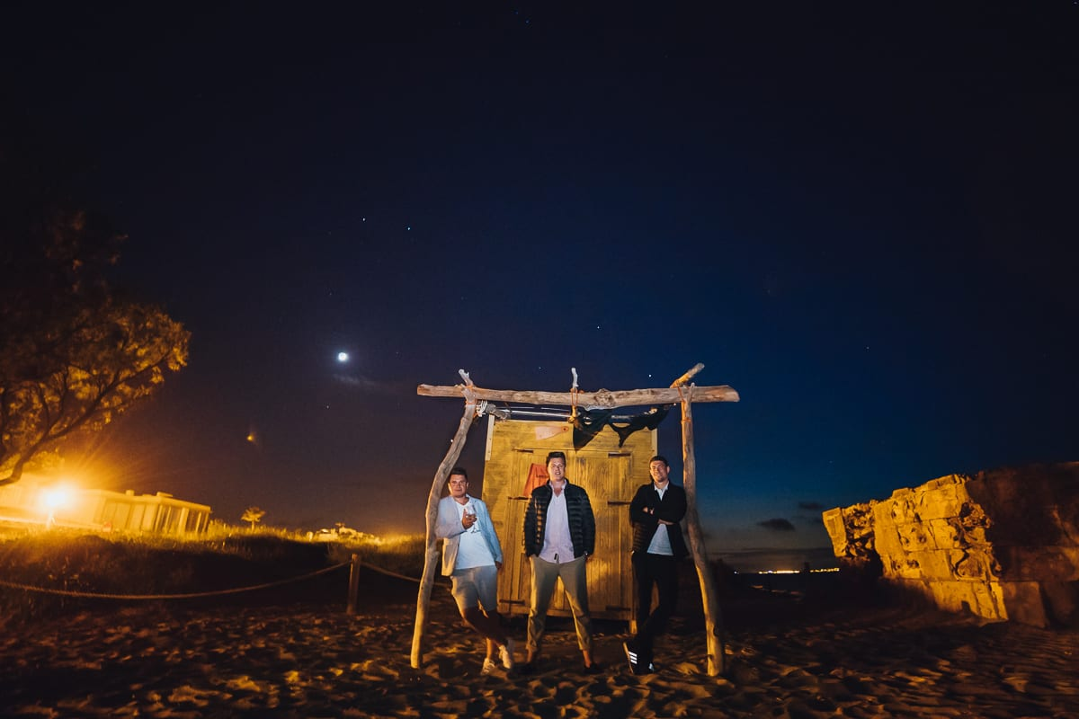 Group photo of the groom with his two best friends in the moonlight and blue hour in front of a server wooden house right on the beach.