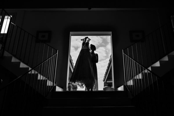 Imposing silhouette photo of the bride and her dress in black and white in front of a large window with illuminated stairs.
