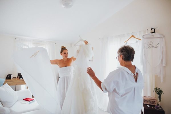 The bride and her mother unpack the wedding dress.