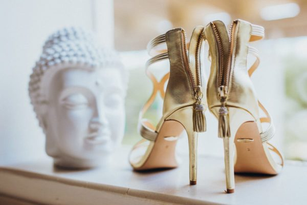 The golden bridal shoes with a white Buddha in the background.