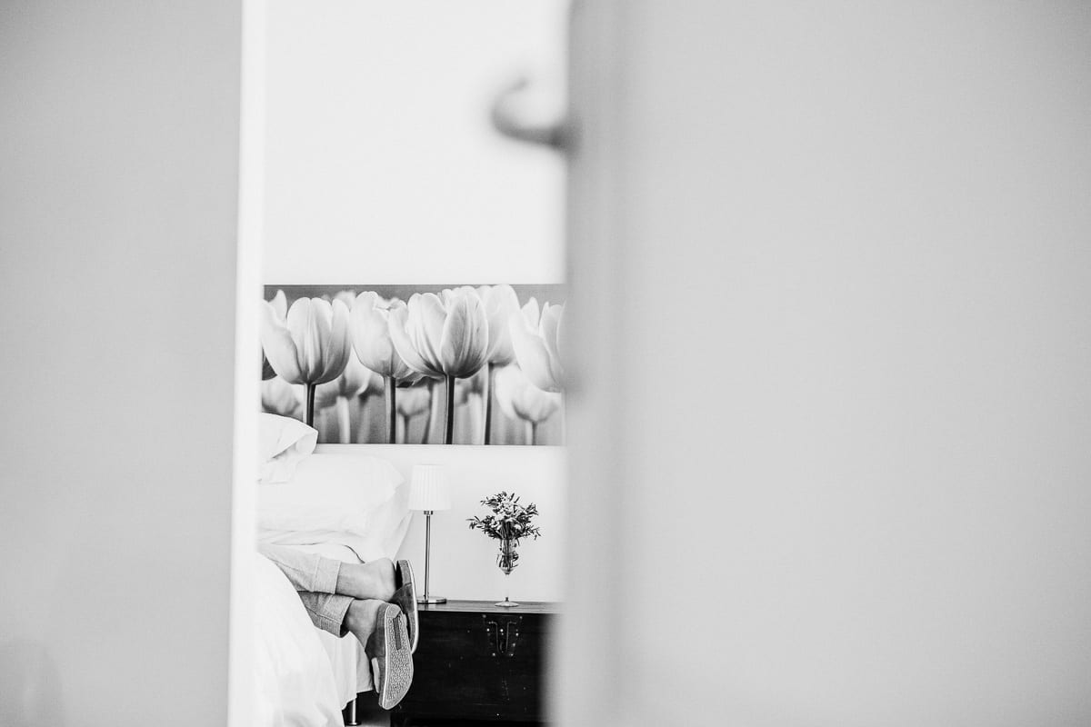 Creative view of the groom's feet. He is lying in the bed. The photo is in black and white.