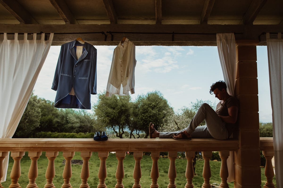 The groom sits comfortably with his phone on the parapet of the veranda of the finca next to his suit that hangs for airing.