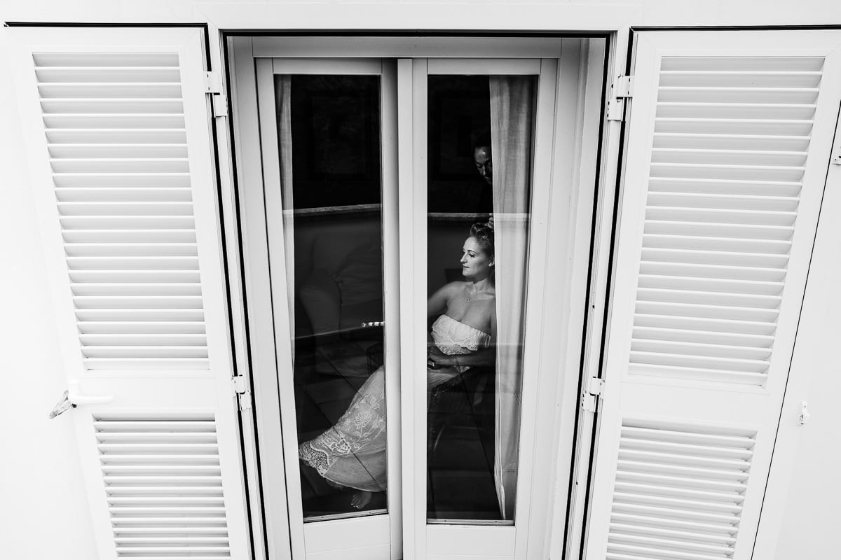 The bride photographed while styling from the outside through the window of the finca.