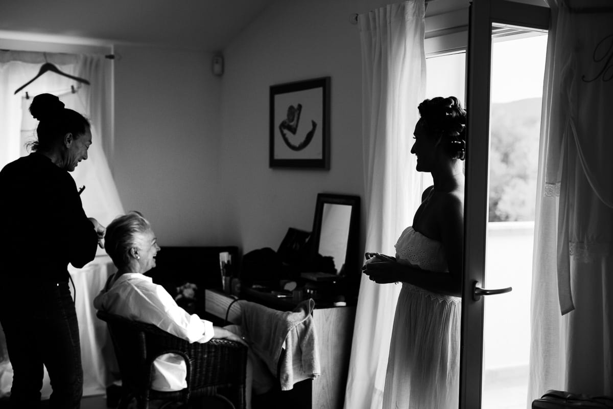 The bride's mother is styled. The bride is standing by the window and watching.