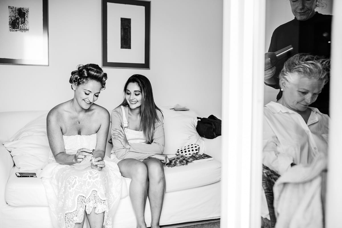 While the bride´s mum is going styled, the bride sits smiling on the bed with a bridesmaid.