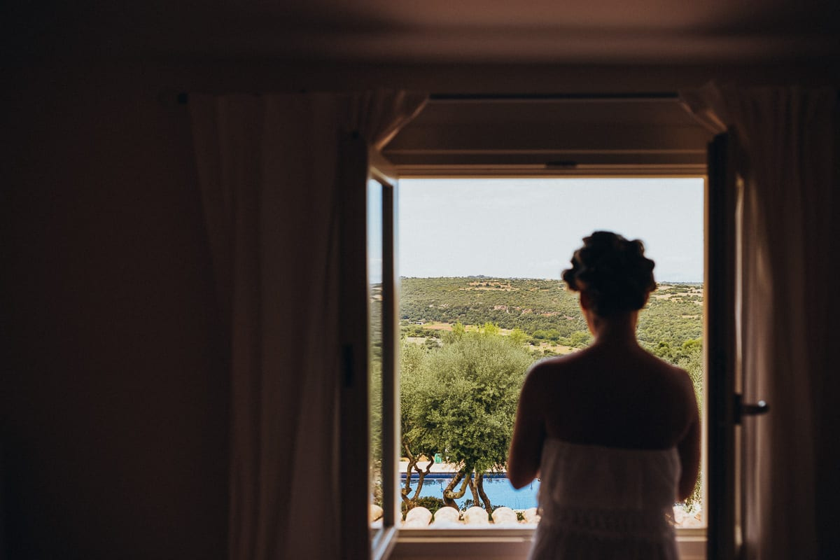 The bride stands by the window and looks into the wide Majorcan landscape.
