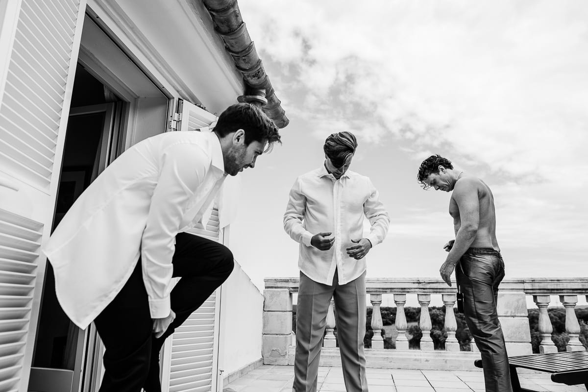 The mens put on their suits on the terrace of the wedding finca being at the fresh air.