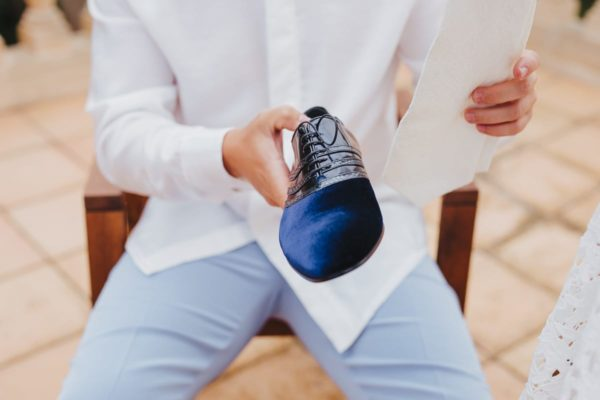 The groom holds one of his shoes in his hand to put it on.