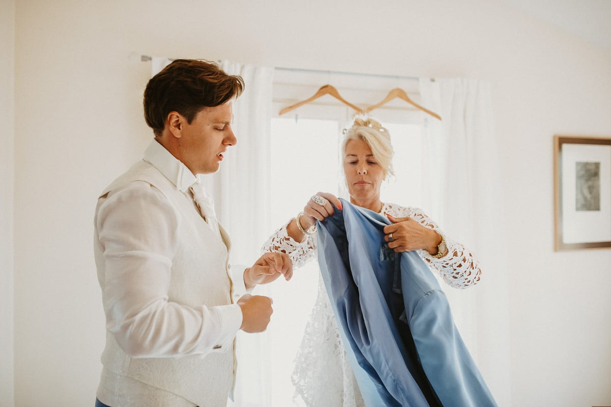 The mother helps her son while putting on the jacket.