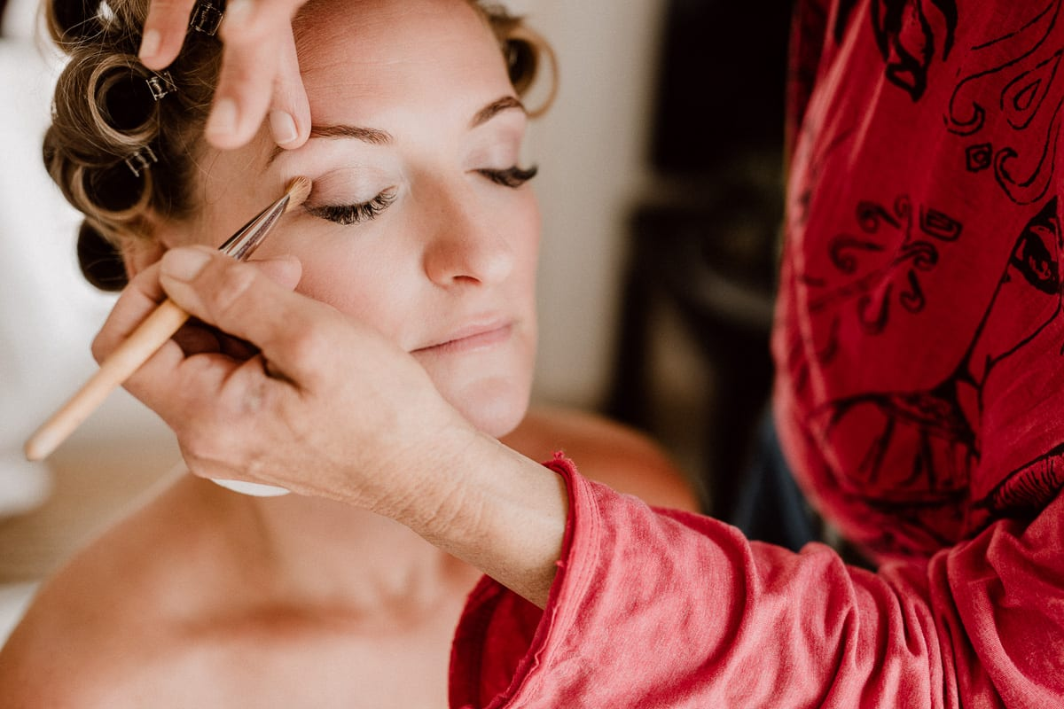 Beautiful close-up of the bride while she is made up by her wedding make up artist.