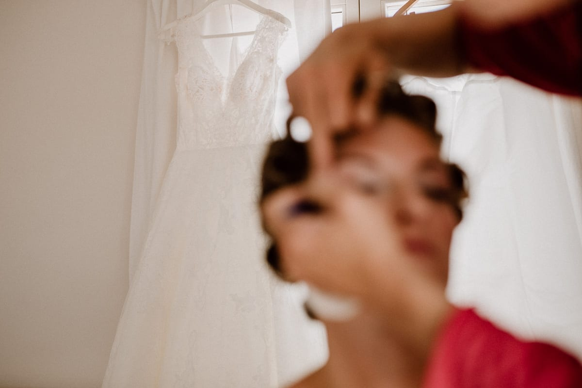 Snapshot during make-up with the focused wedding dress in the background and the blurred bride in the foreground.