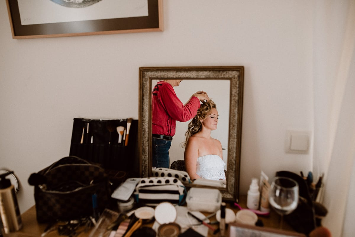 The bride with opened curly hair in the mirror.