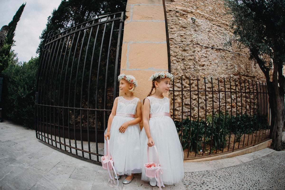 The little bridesmaids stand at the entrance of the church and wait for the bride to come.