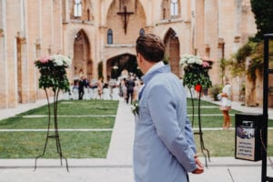 The groom is waiting at the entrance of the church.