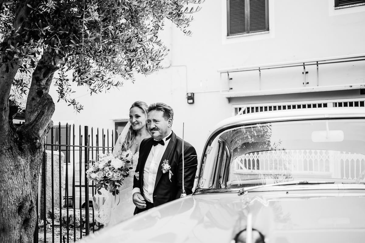 The father and his daughter got out of the vintage wedding car.