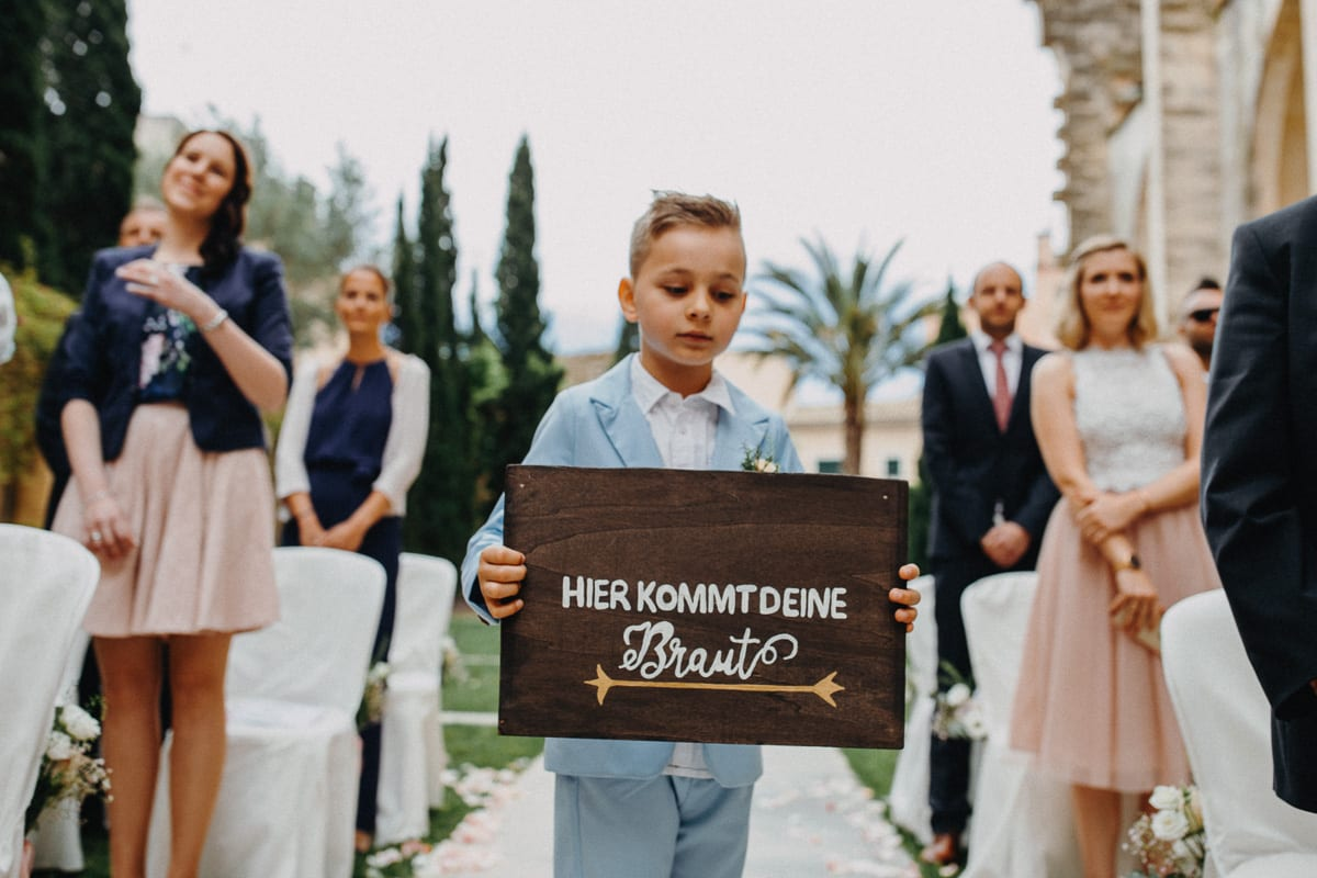 A little boy in anticipation with the sign Here comes your bride.