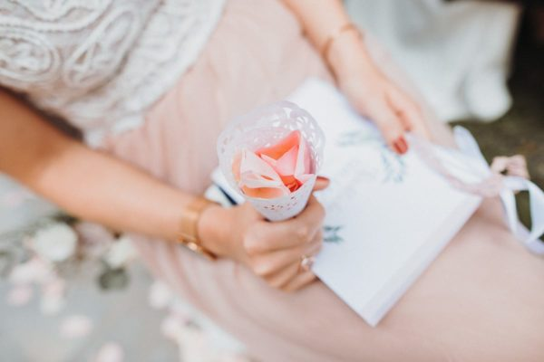 Close-up of a sitting guest holding the rose petals.