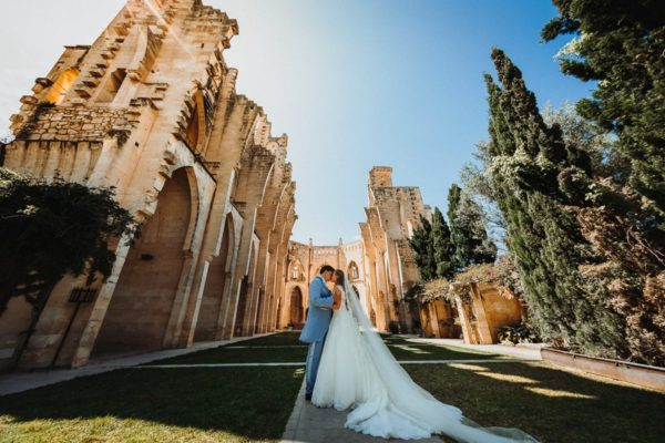 Impressive super wide-angle shot of the kissing bridal couple in front of the imposing roofless church Iglesia Nova in Majorca.