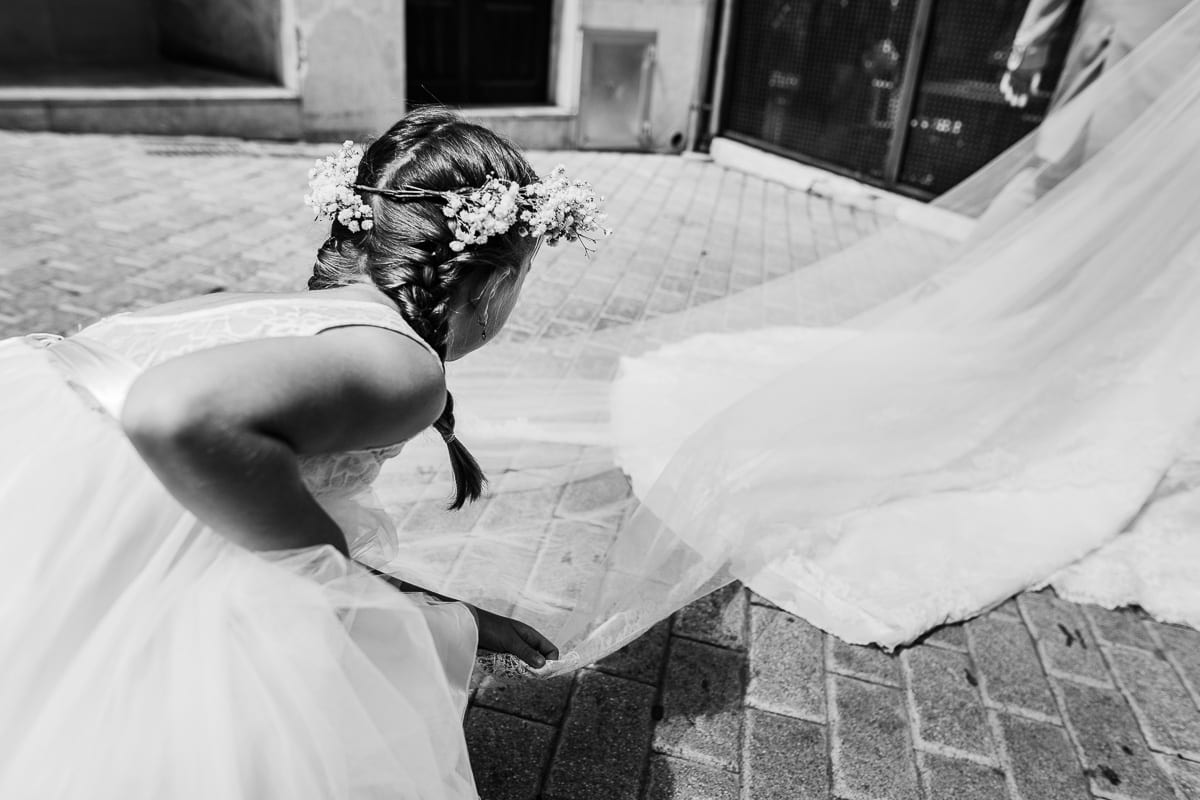 The flower girl turns the veil on the bride while walking.