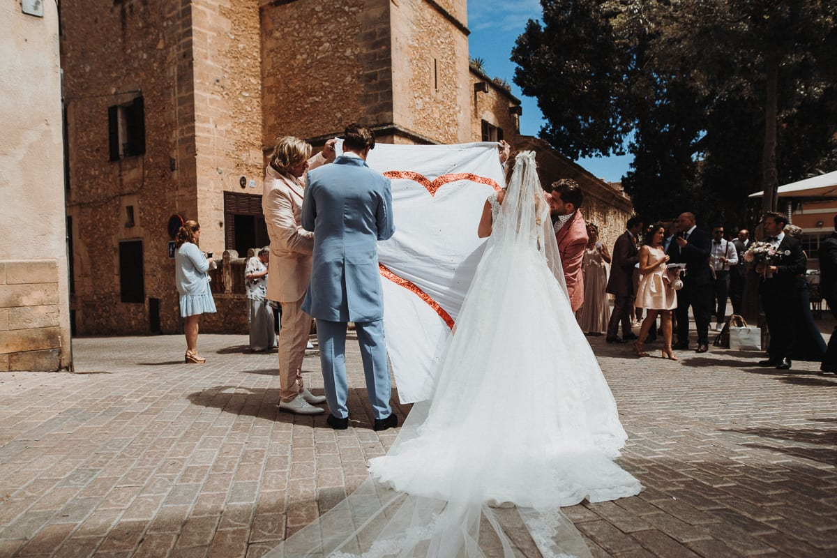 On the market square in Son Servera. The wedding party is waiting for the bridal couple with a big heart.