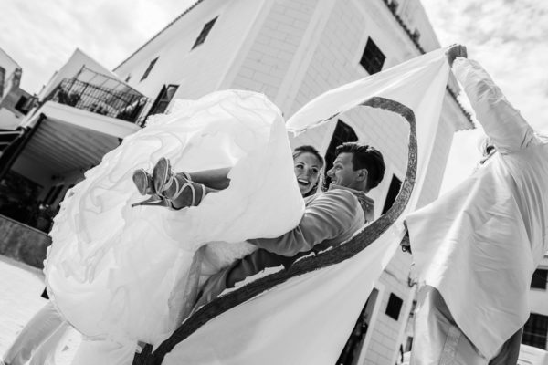 The groom carries his bride through the cut-out heart.