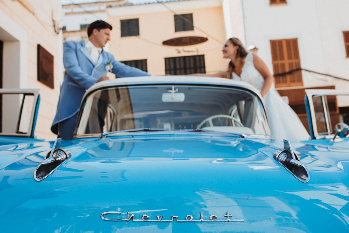 The bride and groom shortly before they start to drive in their the vintage oldtimer car back to the wedding finca.