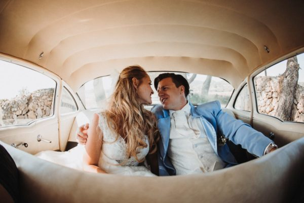 The engaged bride and groom while driving in their wedding car.