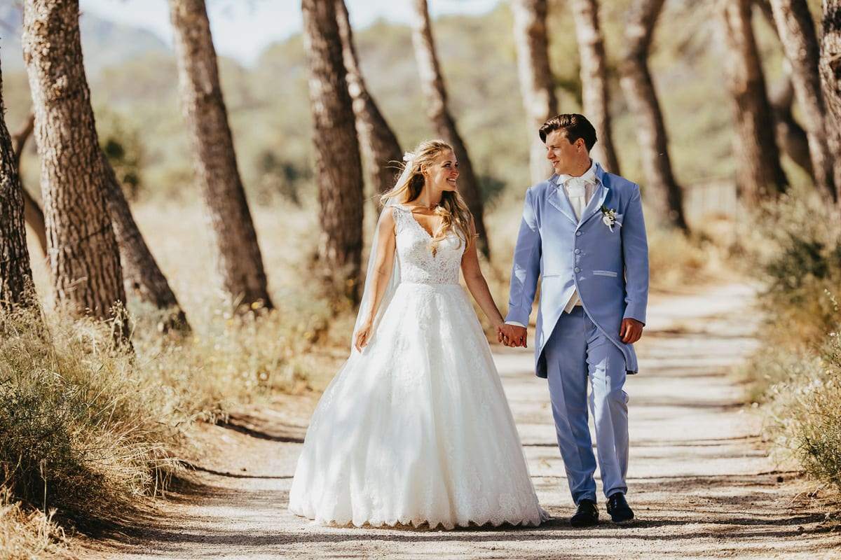 The newlyweds walking hand in hand through the pine alley near Son Servera.