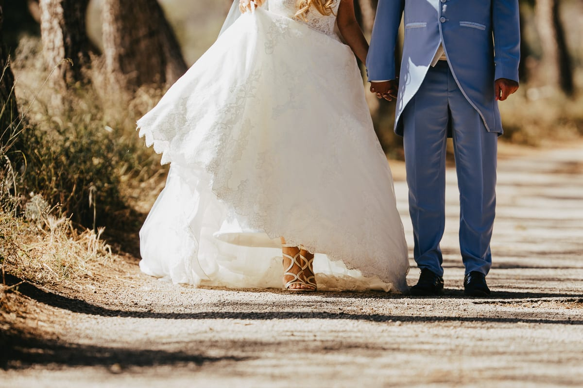 The feets of the bride with her beautiful bridal shoes on the sandy path near Son Servera.