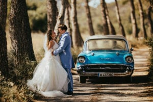 The hugging newlyweds in front of the classic car among green pine trees.