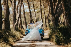 The newlyweds dance in front of the vintage car in nature.