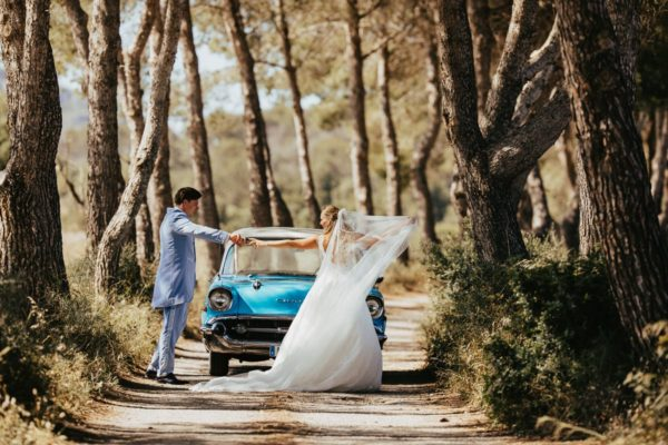 Snapshot of the happy newlyweds dancing between the green nature with their wedding car.