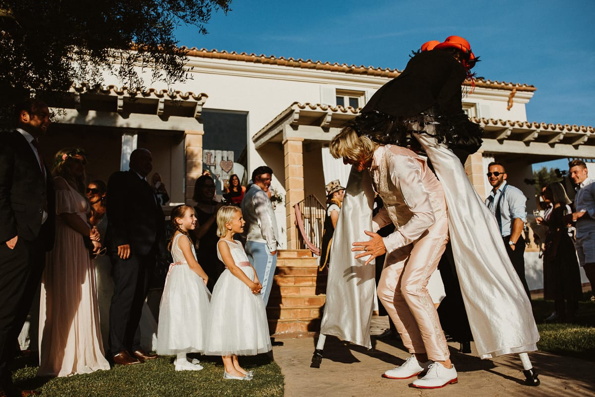The father of the groom passes laughing through the entertainers on stilts.