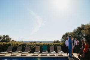 Guests chatting by the pool during the aperitif.
