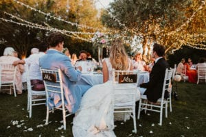 The bridal couple from behind sitting in the evening light at their wedding table.