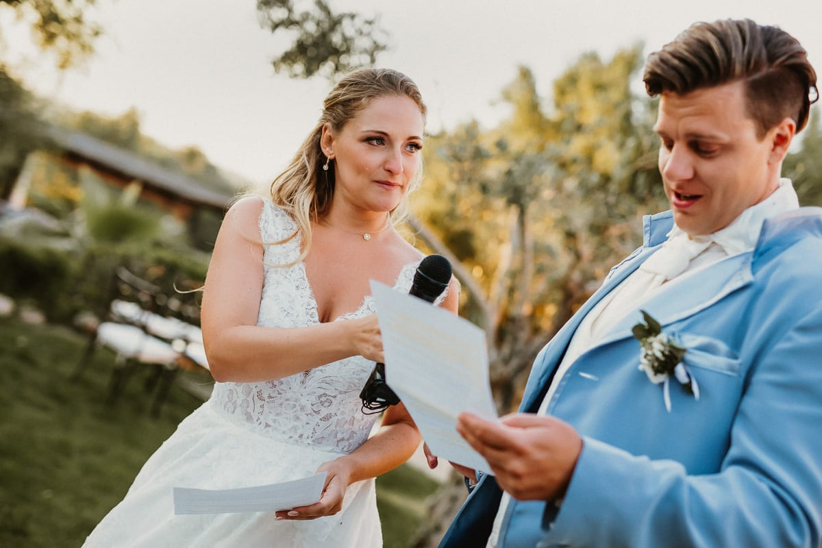 The groom during the opening speech. The bride gives him the microphone. On her face runs a tear.
