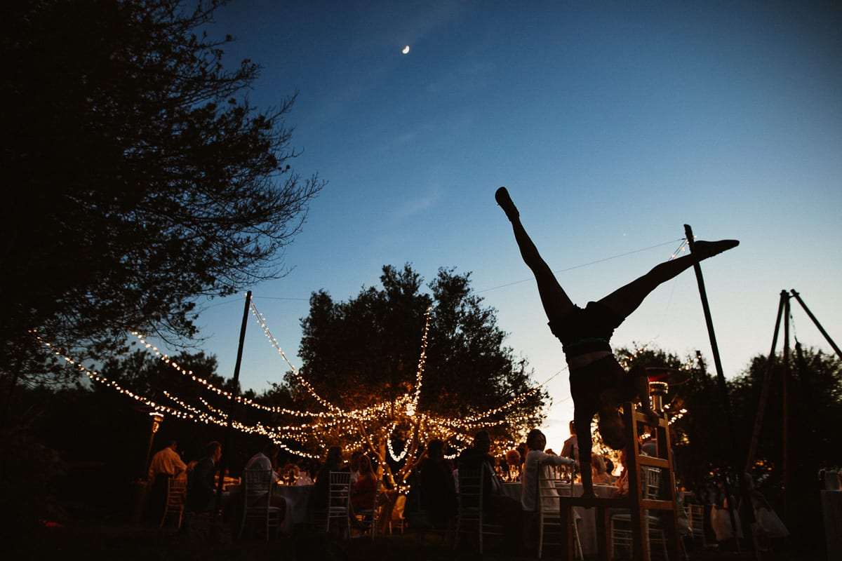 Acrobats performing during the dinner. View of the wedding party dinner tables with the fairy light chain.
